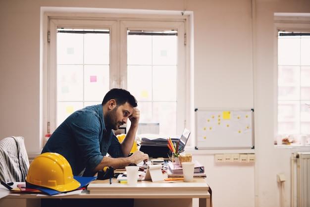Zeer slaperig en vermoeide jonge moderne ingenieursondernemer die rapporten op laptop in zijn bureau bekijkt.