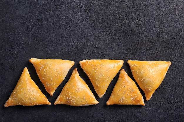 Zeer smakelijke samosa op een zwarte tafel, bovenaanzicht.