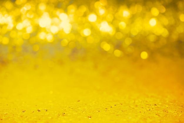 Zeer smal brandpuntsgebied van een glitterachtergrond. goudkleurige pailletten met defocuslicht. kerstmis.