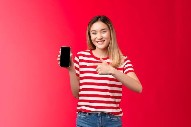 Zeer tevreden vrolijk schattig aziatisch blond meisje dat breed lacht, toont smartphone-display met aanwijsapparaat...