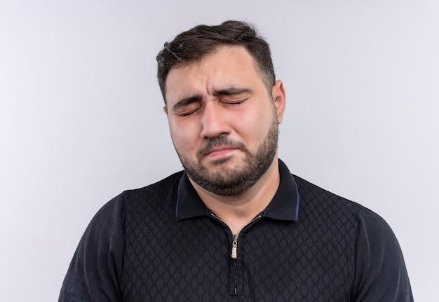 Zeer trieste jonge bebaarde man in zwart shirt met gesloten ogen