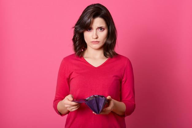 Zeer verdrietig volwassen meisje met lege portemonnee die rechtstreeks naar de camera kijkt, geen geld overhoudt na het winkelen, financiële problemen heeft, geen geldvrouw heeft in een slecht humeur.