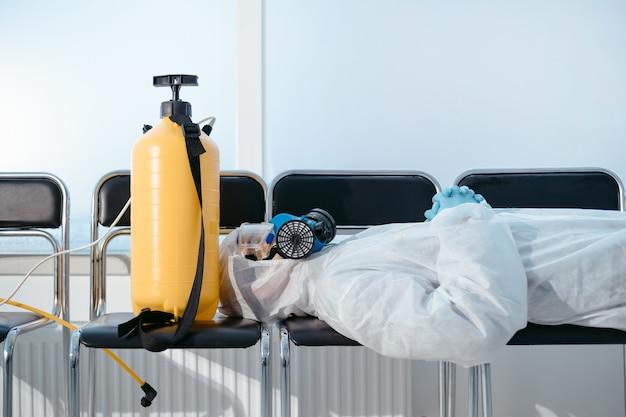 Zeer vermoeide desinfector slaapt op de stoelen in de lobby van het ziekenhuis
