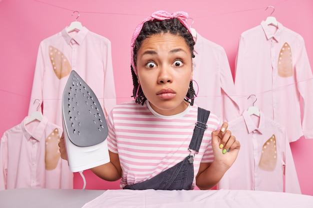 Zeer verraste etnische vrouw met vlechten staart geschokt naar camera bezig met strijken thuis houdt elektrisch strijkijzer gekleed in vrijetijdskleding doet dagelijkse huishoudelijke klusjes staat tegen gestreken shirts