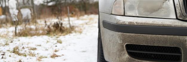 Zeer vieze grijze auto in de herfst of winter in de modder. banner