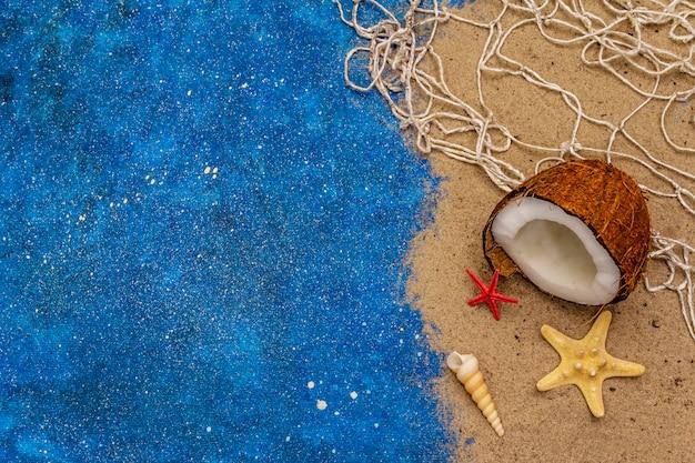 Zeeschelp, zeesterren, kokos touw en blauwe glitter als zee