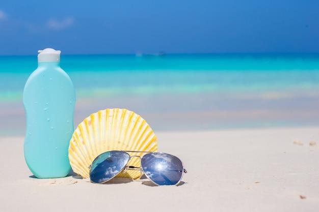 Zeeschelp, zonnebril en zonnebrandcrème op wit zand