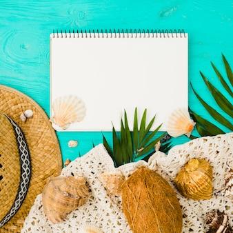 Zeeschelpen en hoed met planten in de buurt van fruit en textiel met kladblok