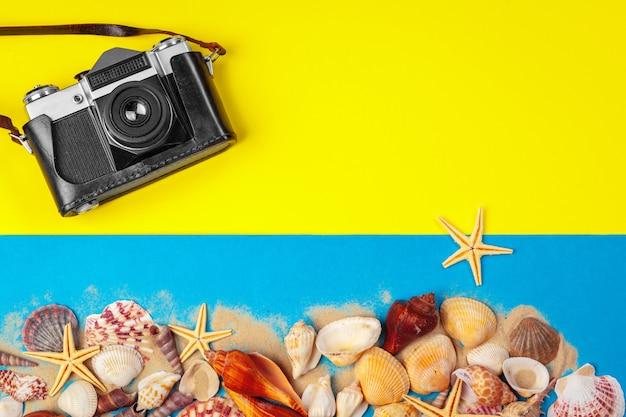 Zeeschelpen en zeesterren en camera op gele achtergrond