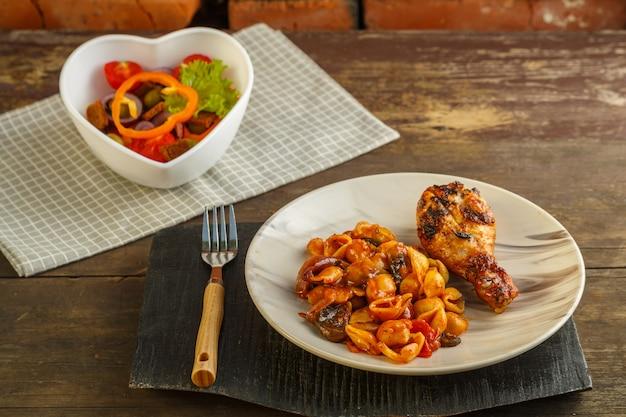 Zeeschelpenpasta in een tomaat met een gegrilde kippenpoot op een standaard en een servet