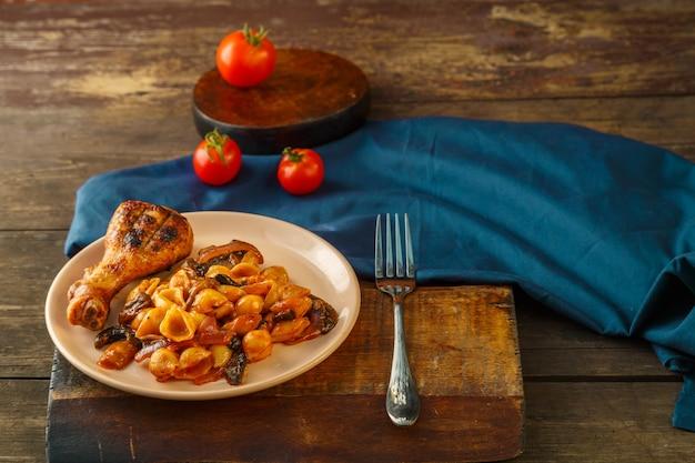 Zeeschelpenpasta in een tomaat met een kippenpoot gebakken op een grill op een standaard