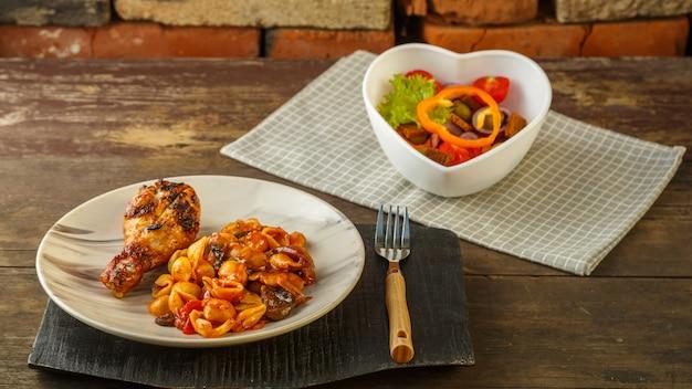 Zeeschelppasta in een tomaat met een gegrilde kippenpoot op een standaard en een servet naast een vork en een groentesalade. horizontale foto