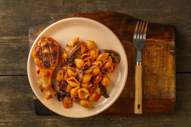 Zeeschelppasta in tomaat en gegrilde kippenpoot op een houten standaard naast een vork.