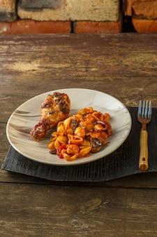 Zeeschelppasta in tomaat en gegrilde kippenpoot op een standaard.