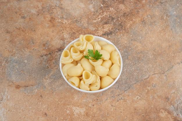 Zeeschelpvormige pasta in kom met peterselie.
