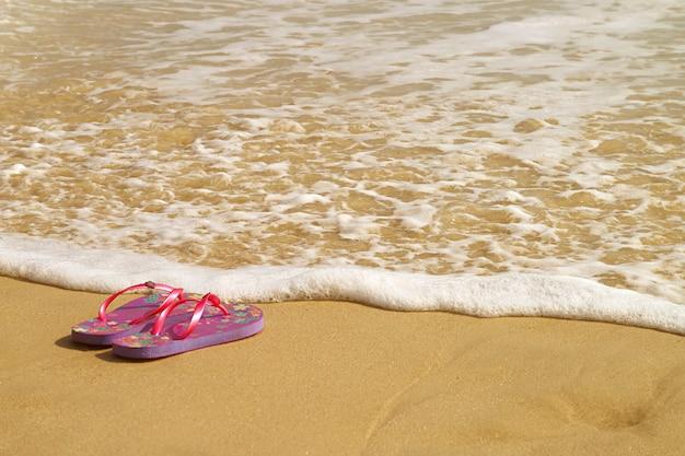 Zeeschuim spettert op het strand een paar sandalen
