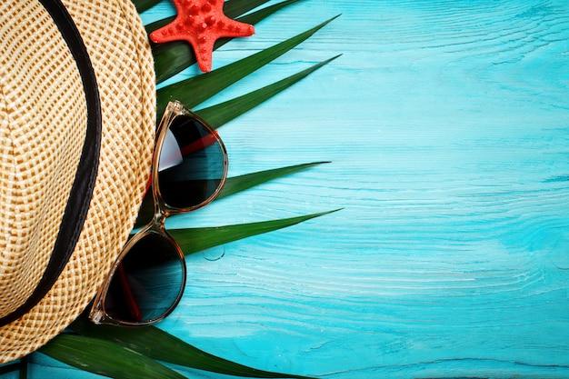 Zeester en palmbladeren die op een blauwe houten oppervlakte liggen