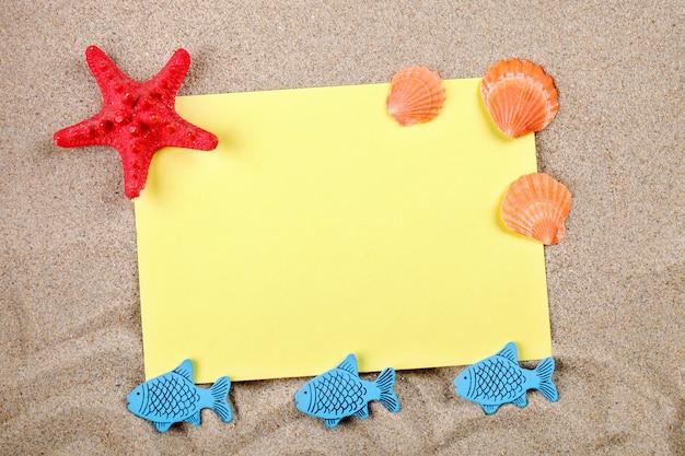 Zeester en zeeschelpen die op het zand op de prentbriefkaar liggen.