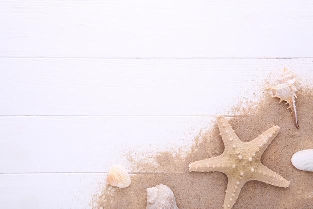 Zeester en zeeschelpen met zand op witte houten met exemplaarruimte. zomer concept