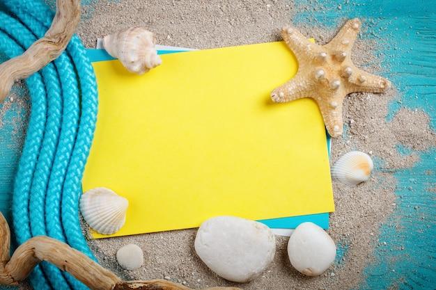 Zeester, kiezels en schelpen liggend op een blauwe houten oppervlak met briefkaart