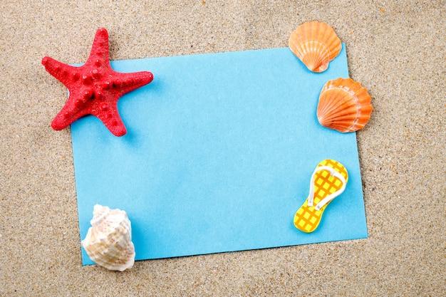 Zeester, kiezelstenen en shells die op het zand op de prentbriefkaar liggen.