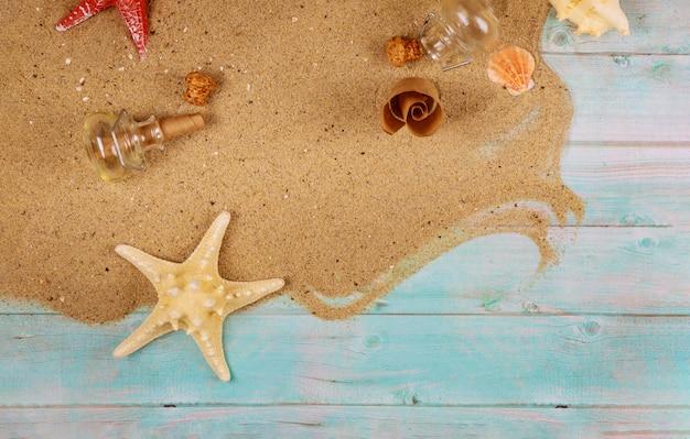 Zeester met schelpen op zand op blauwe houten oppervlak