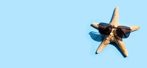 Zeester met zonnebril op blauwe achtergrond. geniet van het concept van de zomervakantie.