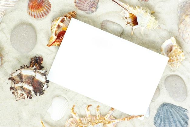 Zeesterren en schelpen een blanco ansichtkaart op zand