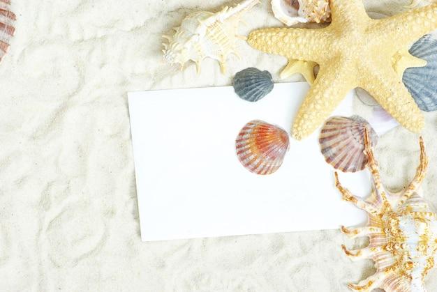 Zeesterren en schelpen een blanco briefkaart op zand