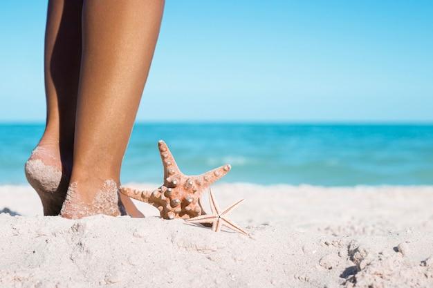 Zeesterren liggen naast vrouwelijke voeten op een zandstrand.