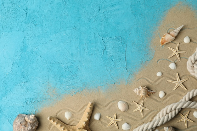 Zeesterren, schelpen, touw en zee zand op blauw, ruimte voor tekst