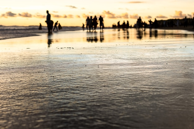 Zeestrand in de avond met onscherpe schaduwmensen met ondiepe focus