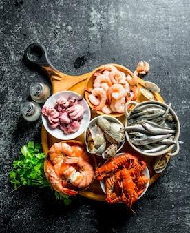Zeevruchten. baby-octopus, langoesten, oesters, garnalen met kruiden en peterselie op donkere rustieke tafel