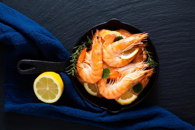 Zeevruchten concept ocean king garnalen gekookt in koekepan ijzer gegoten op zwarte leisteen steen met blauwe servetten