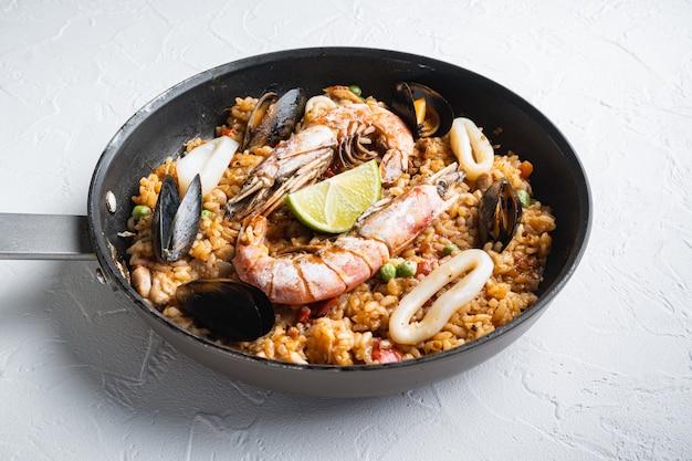 Zeevruchten en kippenpaella met rijst, mosselen, garnalen, kip, tomaten en wijn in pan op witte geweven achtergrond hoogste mening