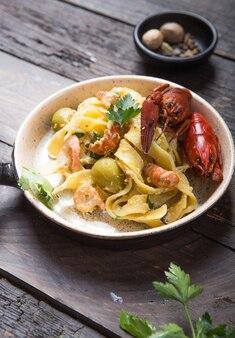 Zeevruchten fettuccine pasta met rivierkreeftjes, octopus garnalen, op stenen pan. gastronomisch gerecht