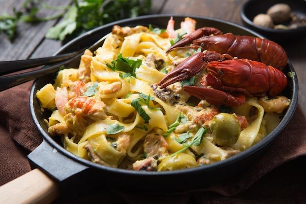 Zeevruchten fettuccine pasta met rivierkreeftjes, octopus shrims, op stenen pan. gastronomisch gerecht