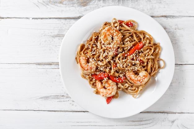 Zeevruchten gebakken udon noedels met garnalen op houten tafel. pad thai