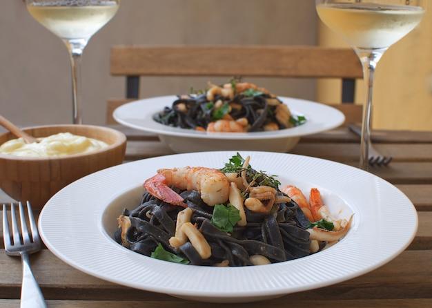 Zeevruchten inktvis inkt pasta close-up garnalen witte wijn alioli