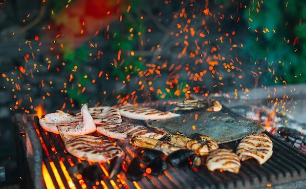 Zeevruchten op de grill, mosselen, garnalen, inktvis en vis worden in vuur en vlam gekookt.