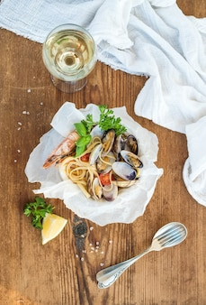 Zeevruchten pasta. spaghetti met kokkels en garnalen in kom, glas witte wijn over rustiek hout