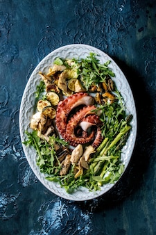 Zeevruchten salade. coocked gegrilde tentakels van octopus, sardines en mosselen op blauwe keramische plaat geserveerd met rucola salade, courgette en asperges over blauwe textuur oppervlak. bovenaanzicht, plat gelegd