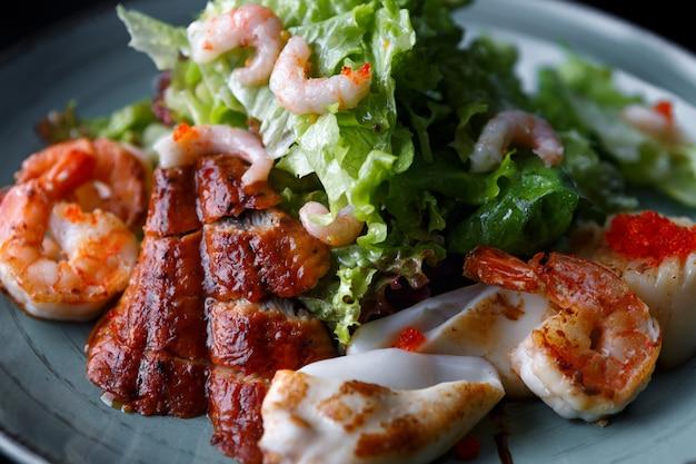 Zeevruchten salade. garnalen, paling, inktvis, sla. tegen een donkere achtergrond.
