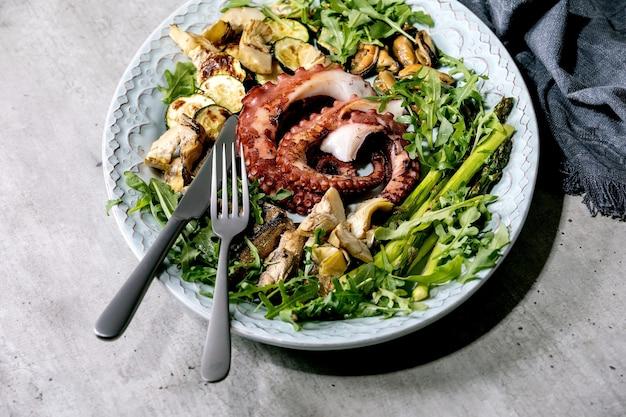 Zeevruchten salade. gekookte gegrilde tentakels van octopus, sardines en mosselen op blauwe keramische plaat geserveerd met rucolasalade, courgette en asperges over grijs oppervlak, stoffen servet
