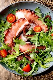 Zeevruchten salade. gekookte tentakels van octopus op blauwe keramische plaat geserveerd met rucola-aragula en cherrytomaatsalade over bruin houten oppervlak en rieten voering. bovenaanzicht, close-up