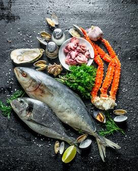 Zeevruchten. verschillende vissen met oesters, krab en baby-octopus. op zwarte rustieke achtergrond