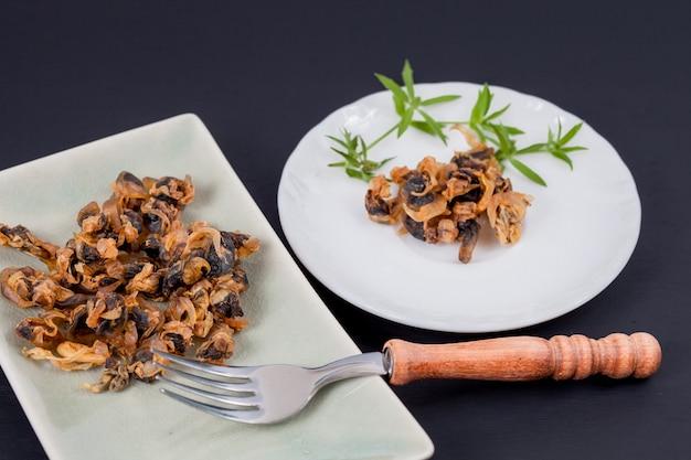 Zeevruchten zoet gedroogde mosselen op schotel met vork