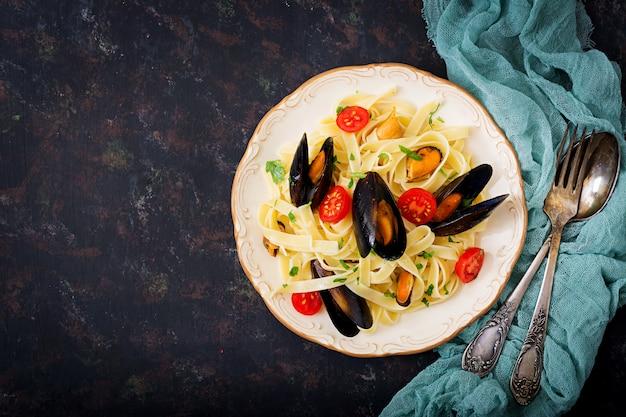 Zeevruchtenfettuccinedeegwaren met mosselen over zwarte lijst. mediterraan delicatesse eten. plat leggen. bovenaanzicht