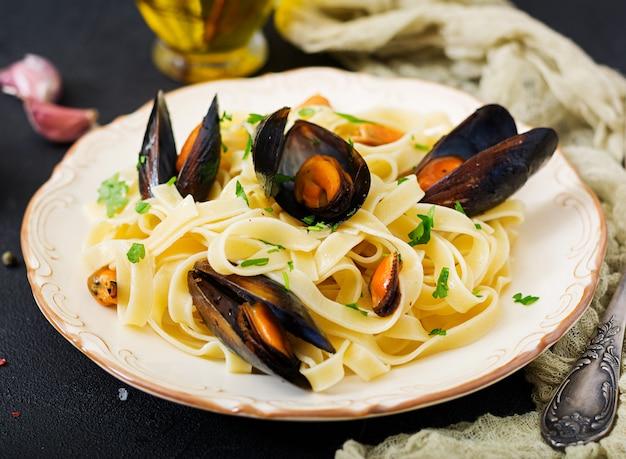 Zeevruchtenfettuccinedeegwaren met mosselen over zwarte lijst. mediterraan delicatesse eten.