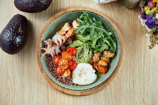 Zeevruchtenkom met avocado, quinoa, octopus, mosselen, kerstomaatjes en gepocheerd ei. boeddha schaal met gezond en uitgebalanceerd voedsel. bovenaanzicht, plat lag